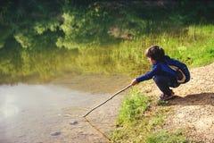 Child play fishing near lake. stock photo