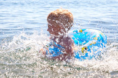 Little kid play in water and making splash Royalty Free Stock Photography