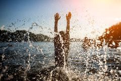 Little kid play in water and making splash; Stock Images