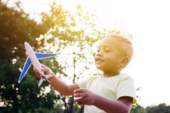 Little kid playing with airplane toy in green park. During sunlight Stock Images