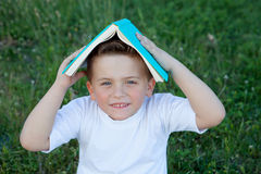 Little kid playing with a book at outside Stock Photo