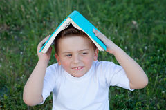 Little kid playing with a book at outside Royalty Free Stock Image