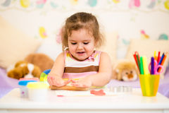 Little kid playing with colorful clay Stock Photos