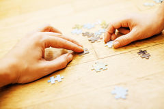 Little kid playing with puzzles on wooden floor together with pa Royalty Free Stock Images