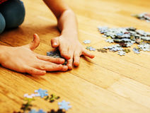 Little kid playing with puzzles on wooden floor together with pa Stock Photo