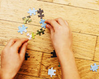 Little kid playing with puzzles on wooden floor together with parent, lifestyle people concept, loving hands to each Royalty Free Stock Photos