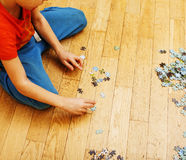 Little kid playing with puzzles on wooden floor together with parent, lifestyle people concept, loving hands to each Royalty Free Stock Image