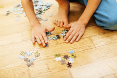 Little kid playing with puzzles on wooden floor together with parent, lifestyle people concept, loving hands to each Royalty Free Stock Photography