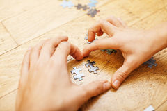 Little kid playing with puzzles on wooden floor together with parent, lifestyle people concept, loving hands to each Stock Image