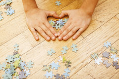 Little kid playing with puzzles on wooden floor together with parent, lifestyle people concept, loving hands to each Stock Photo