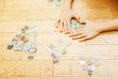 Little kid playing with puzzles on wooden floor together with parent, lifestyle people concept, loving hands to each Stock Photography