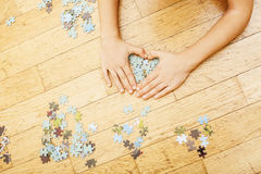 Little kid playing with puzzles on wooden floor together with parent, lifestyle people concept, loving hands to each Stock Photos
