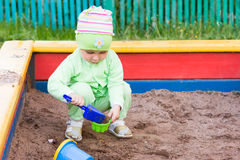 Little kid playing in a sandbox Stock Images