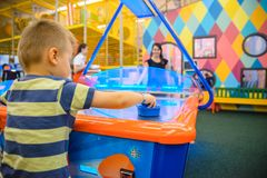 Little kid plays in air hokey. In Entertainment Center stock photo