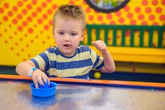 Little kid plays in air hokey. In Entertainment Center royalty free stock images
