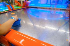 Little kid plays in air hokey. In Entertainment Center stock images