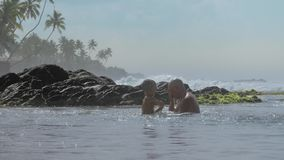 Little kid plays with daddy splashing ocean water at rocks