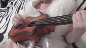 Little kid plays the guitar, hands fingering stock footage