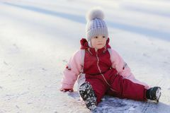 Little baby is sitting on the snow at sunset. Little kid plays in the street in winter Stock Photo