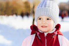Portrait of a little baby in the street in winter. Little kid plays in the street in winter Royalty Free Stock Images