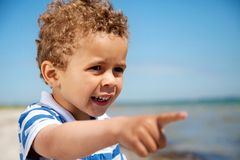 Little Kid Pointing at Something Interesting. Adorable little kid pointing at something interesting outdoors royalty free stock photos