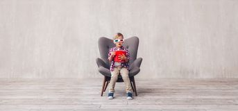 Little kid with popcorn in 3d glasses. At home royalty free stock image