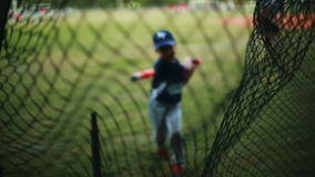 Little Kid practing how to bat at a baseball field
