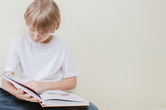 Little kid reading a book. Education, school, leisure concept Royalty Free Stock Images