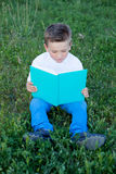 Little kid reading a book at outside. Little kid sitting on the grass reading a book Royalty Free Stock Image