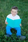 Little kid reading a book at outside. Little kid sitting on the grass reading a book Royalty Free Stock Photos