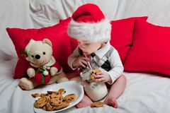 A little kid in a red cap eats a cookies and milk. Christmas photography of a baby in a red cap. New Year holidays and Christmas royalty free stock photography
