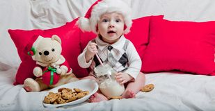 A little kid in a red cap eats a cookies and milk. Christmas photography of a baby in a red cap. New Year holidays and Christmas.  royalty free stock photo
