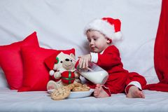 A little kid in a red cap eats a cookies and milk. Christmas photography of a baby in a red cap. New Year holidays and Christmas.  stock images