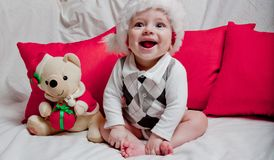 A little kid in a red cap eats a cookies and milk. Christmas photography of a baby in a red cap. New Year holidays and Christmas.  stock photos