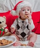 A little kid in a red cap eats a cookies and milk. Christmas photography of a baby in a red cap. New Year holidays and Christmas.  stock photography