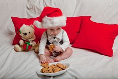 A little kid in a red cap eats a cookies and milk. Christmas photography of a baby in a red cap. New Year holidays and Christmas.  royalty free stock photos