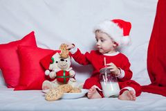 A little kid in a red cap eats a cookies and milk. Christmas photography of a baby in a red cap. New Year holidays and Christmas.  royalty free stock image
