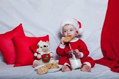 A little kid in a red cap eats a cookies and milk. Christmas photography of a baby in a red cap. New Year holidays and Christmas.  royalty free stock images