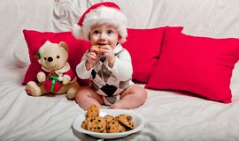 A little kid in a red cap eats a cookies and milk. Christmas photography of a baby in a red cap. New Year holidays and Christmas.  stock photo