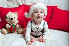 A little kid in a red cap eats a cookies and milk. Christmas photography of a baby in a red cap. New Year holidays and Christmas.  royalty free stock photography