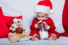 A little kid in a red cap eats a cookies and milk. Christmas photography of a baby in a red cap. New Year holidays and Christmas. N royalty free stock image