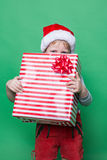 Little Kid in red costume of dwarf hiding behind red gift box. Studio portrait over green background Stock Photo
