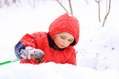 Little kid in red jacket playing in snow Stock Photos