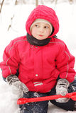 Little kid in red jacket sitting with shovel Royalty Free Stock Photo
