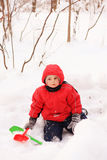 Little kid in red jacket sitting on snow Stock Photography