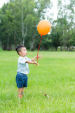 Little kid relaese the orange balloon Royalty Free Stock Photo