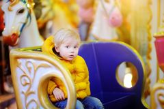 Little Kid Riding On Colorful Carousel Merry Go Round. City Outdoors Entertainment For Children Stock Images