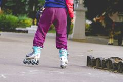 Little kid riding the roller skates in the street f stock photos