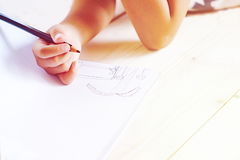 Little kid`s hand drawing something on white paper. Stock Photography