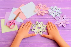 Little kid shows paper snowflakes. Children hands on lilac wooden table. Beautiful colored snowflakes diy cut from paper royalty free stock photography